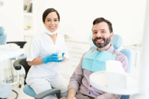 Confident Good Looking Female Orthodontist Holding Smile Design Model While Sitting By Patient