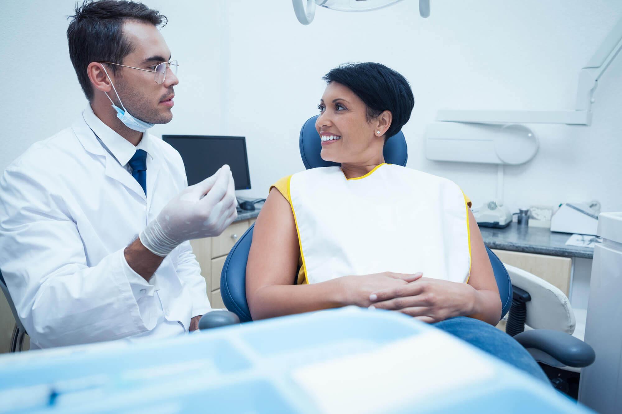 Male Dentist Examining Womans Teeth
