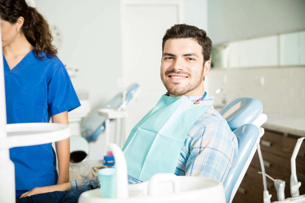 Portrait Of Smiling Man Sitting On Chair While Female Dentist Working In Clinic